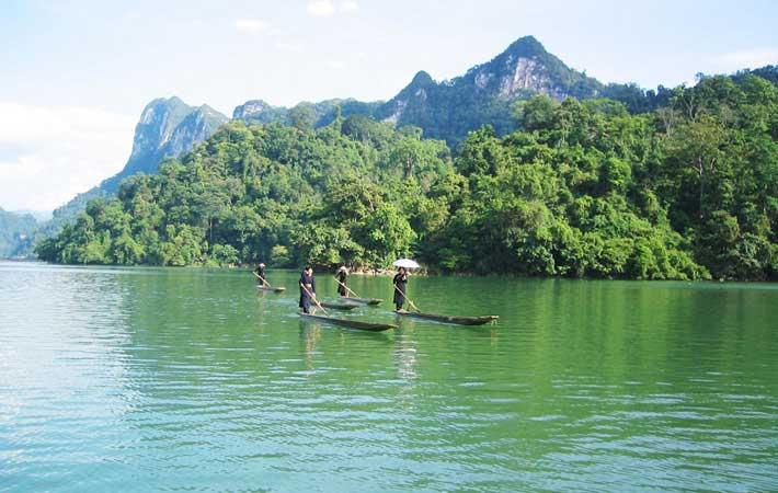 Gente local en piraguas en el lago Ba Be Vietnam