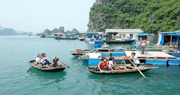 Niños rumbo a la escuela en un pueblo flotante en la Bahia de Halong