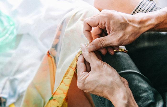 Costura a  mano del vetsido vietnamita ai dai
